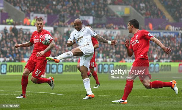 Andre Ayew of Swansea City misses an early chance at goal watched by Martin Skrtel of Liverpool during the Barclays Premier League match between...