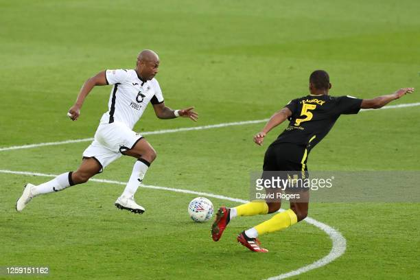 Andre Ayew of Swansea City runs with the ball under pressure from Ethan Pinnock of Brentford during the Sky Bet Championship Play Off Semifinal 1st...