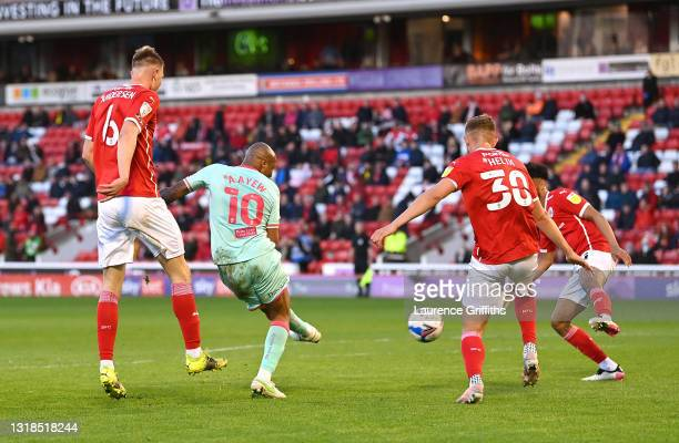 Andre Ayew of Swansea City scores his team's first goal while under pressure from Mads Juel Andersen and Michal Helik of Barnsley FC during the Sky...