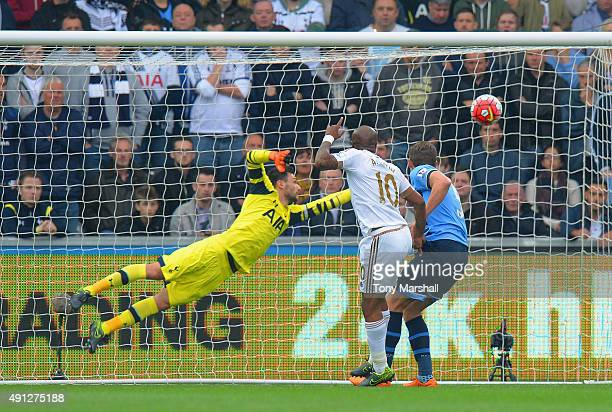 Andre Ayew of Swansea City scores the opening goal past Harry Kane of Tottenham Hotspur during the Barclays Premier League match between Swansea City...