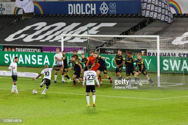 Andre Ayew of Swansea City takes a free kick inside the Stoke City box while goalkeeper Angus Gunn of Stoke City is joined by all his team mates on...