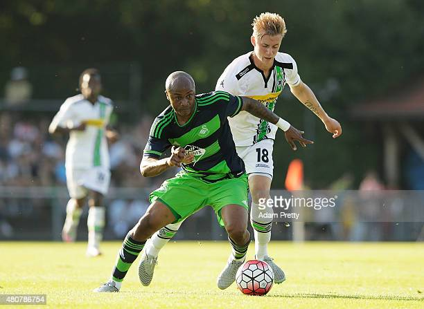 Andre Ayew of Swansea is challenged by Marvin Schulz of Borussia Moenchengladbach during the City Preseason Friendly between Borussia...