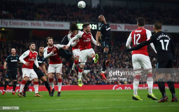 Andre Ayew of West Ham heads above Mathieu Debuchy of Arsenal during the Carabao Cup Quarter Finals match between Arsenal and West Ham United at...