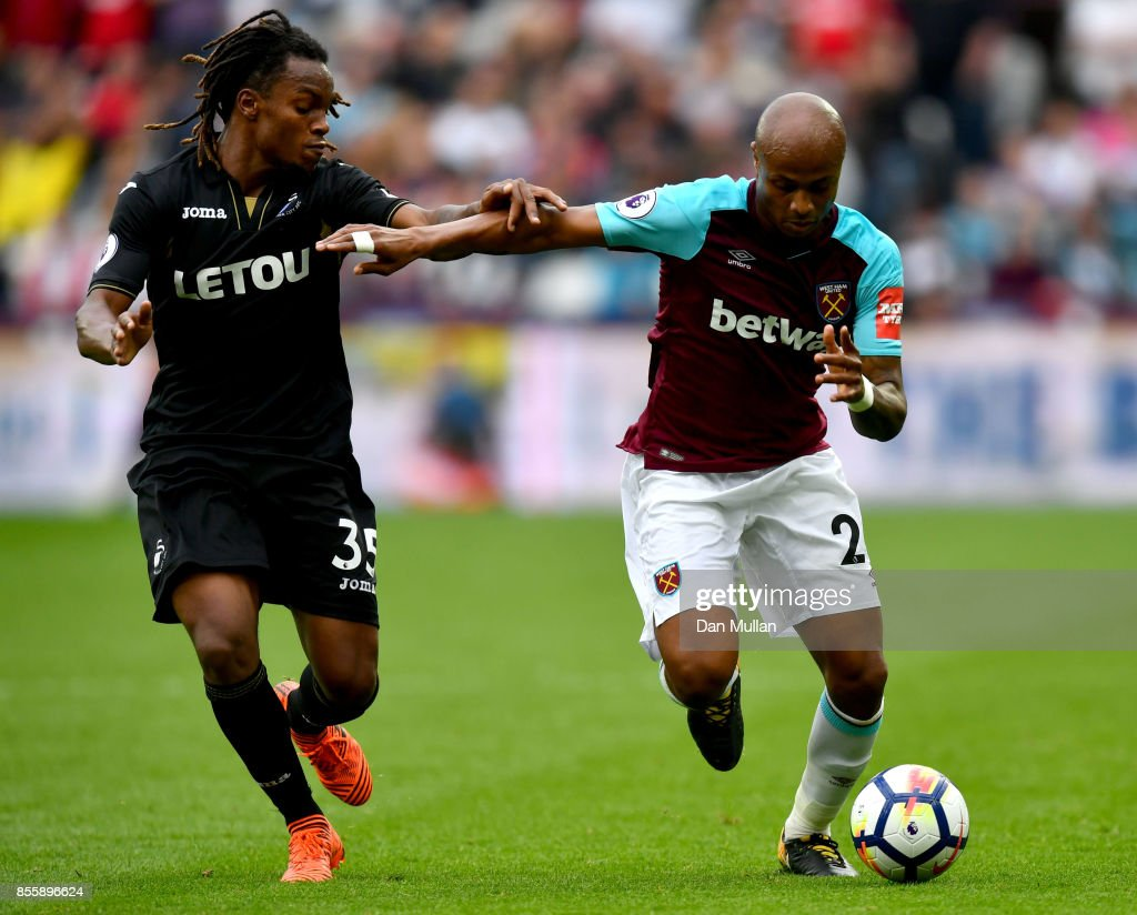 Andre Ayew of West Ham United and Renato Sanches of Swansea City compete for the ball during the Premier League match between West Ham United and Swansea City at London Stadium on September 30, 2017 in London, England.