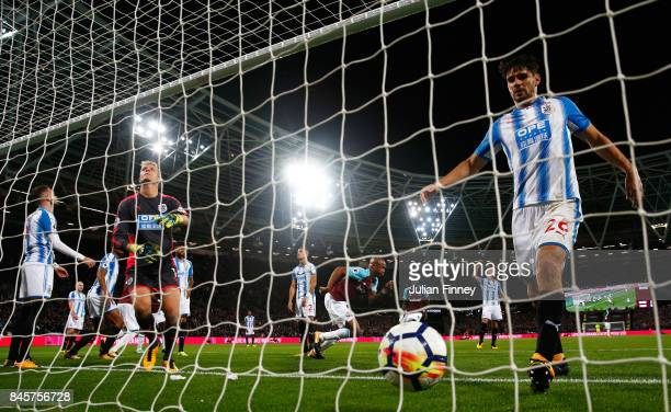 Andre Ayew of West Ham United celebrates as he scores their second goal as Christopher Schindler of Huddersfield Town collects the ball in the net...