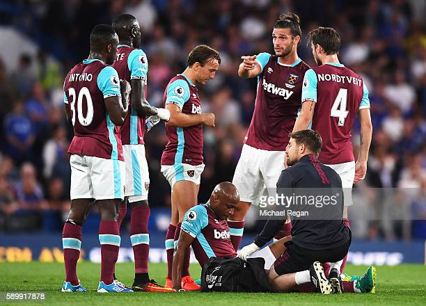 Andre Ayew of West Ham United is treated by the physio following an injury during the Premier League match between Chelsea and West Ham United at...
