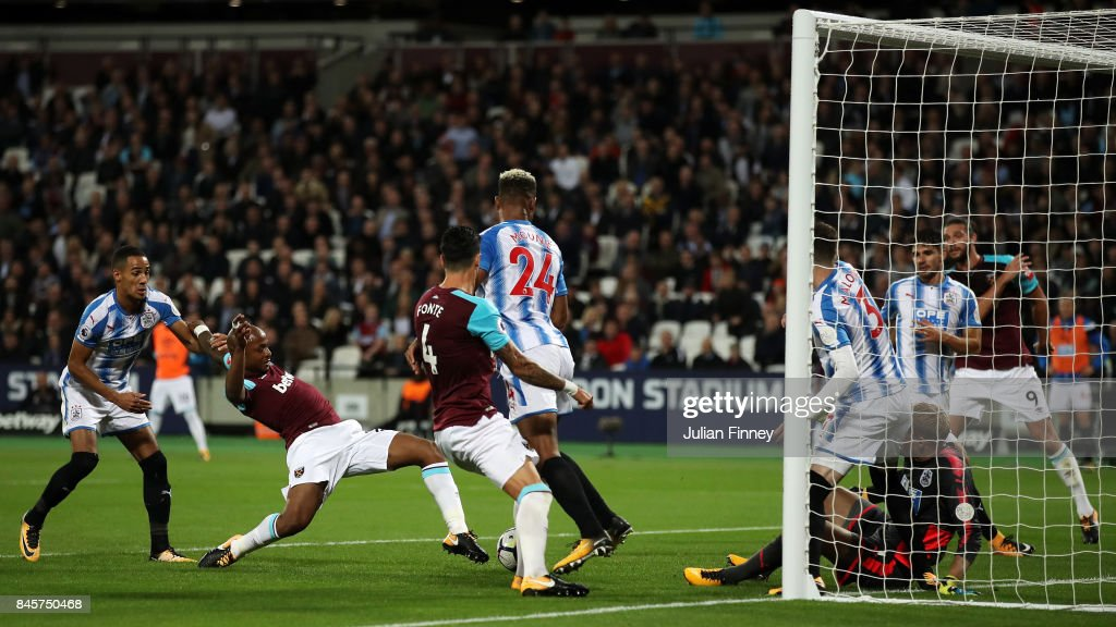 Andre Ayew of West Ham United (2L) scores their second goal during the Premier League match between West Ham United and Huddersfield Town at London Stadium on September 11, 2017 in London, England.