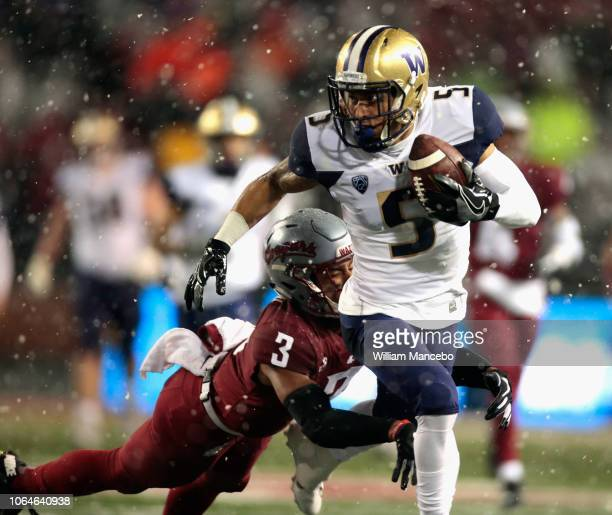 Andre Baccellia of the Washington Huskies carries the ball against Darrien Molton of the Washington State Cougars in the first half at Martin Stadium...