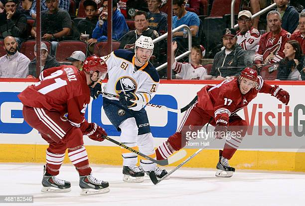 Andre Benoit of the Buffalo Sabres flips the puck up in the air over the sticks of Jordan Szwarz and John Moore of the Arizona Coyotes during the...