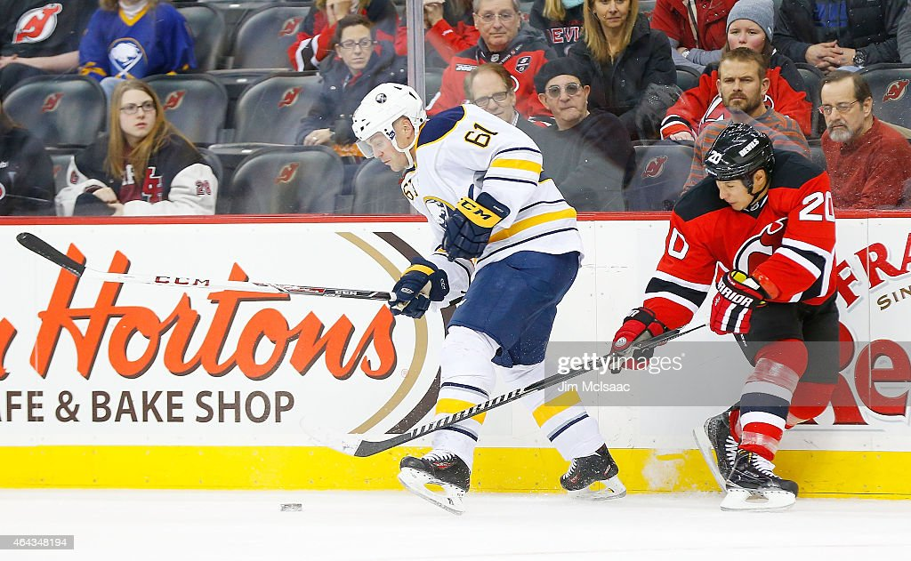 Andre Benoit #61 of the Buffalo Sabres in action against Jordin Tootoo #20 of the New Jersey Devils at the Prudential Center on February 17, 2015 in Newark, New Jersey. The Devils defeated the Sabres 2-1 after a shootout.