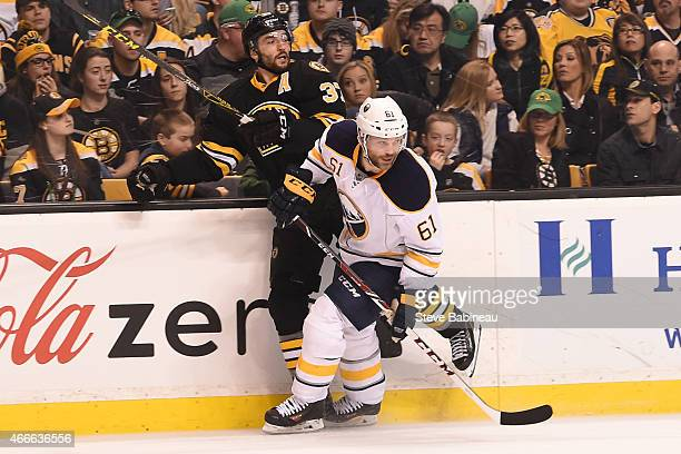 Andre Benoit of the Buffalo Sabres skates against Patrice Bergeron of the Boston Bruins at the TD Garden on March 17 2015 in Boston Massachusetts
