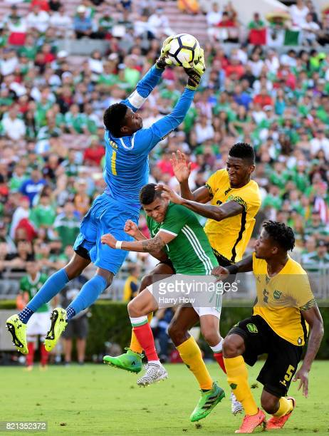 Andre Blake of Jamaica leaps to grab the ball from Orbelin Pineda of Mexico as Damion Lowe and Alvas Powell defend during the first half of the...