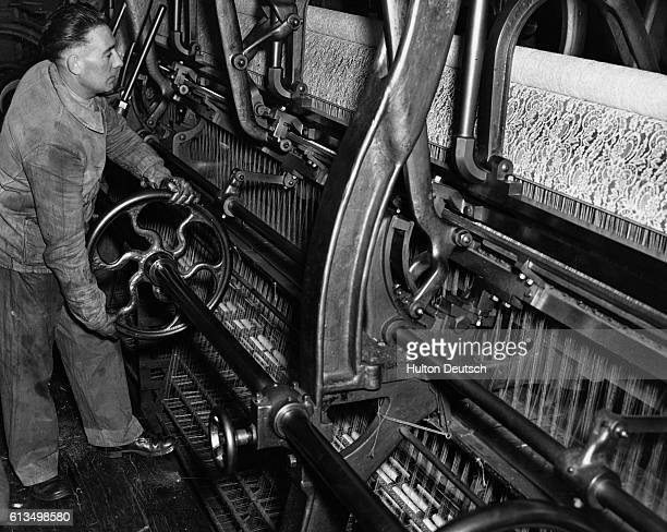 Andre Brulin the foreman at a French lace factory operates a power loom