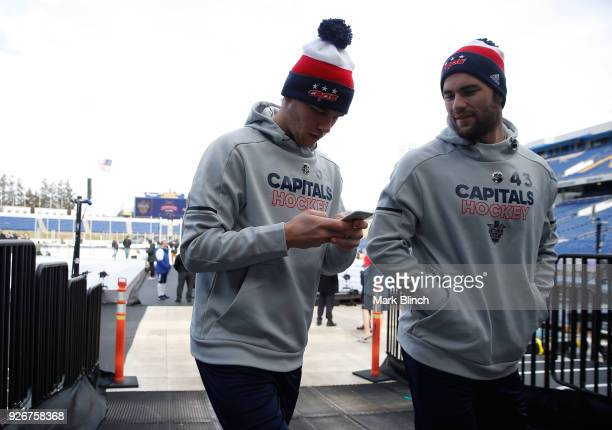 Andre Burakovsky and Tom Wilson of the Washington Capitals walk back to the locker room after checking the ice surface prior to the Coors Light NHL...