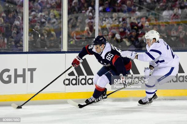 Andre Burakovsky of the Washington Capitals and Travis Dermott of the Toronto Maple Leafs battle for the puck in the first period of the 2018 Coors...