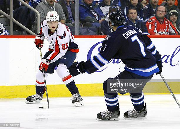 Andre Burakovsky of the Washington Capitals plays the puck down the ice as Ben Chiarot of the Winnipeg Jets defends during third period action at the...