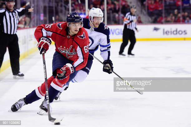 Andre Burakovsky of the Washington Capitals skates with the puck against Andrew Copp of the Winnipeg Jets in the first period at Capital One Arena on...