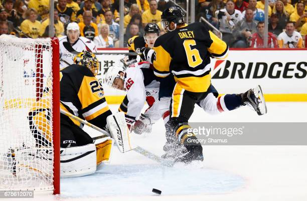 Andre Burakovsky of the Washington Capitals tries to get a shot off on goalie MarcAndre Fleury of the Pittsburgh Penguins while taking a check from...