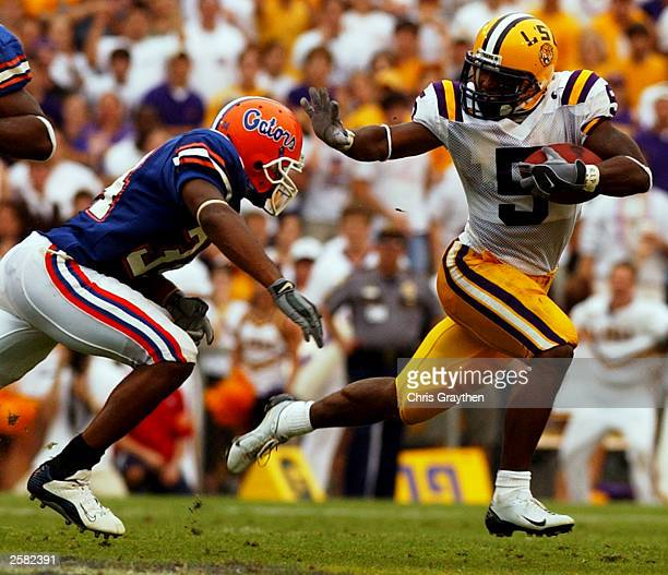 Andre Caldewell of the Louisiana State University Tigers avoids a tackle from Daryl Dixon of the University of Florida Gators on October 11 2003 at...