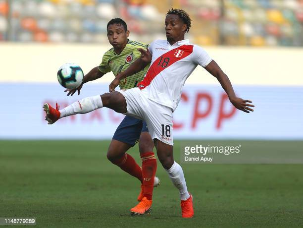 Andre Carrillo of Peru and Luis Muriel of Colombia compete for the ball during a friendly match between Peru and Colombia at Estadio Monumental on...