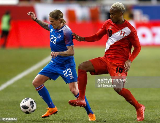 Andre Carrillo of Peru fights for the ball with Ari Freyr Skúlason of Iceland during their friendly match at Red Bull Arena on March 27 2018 in...