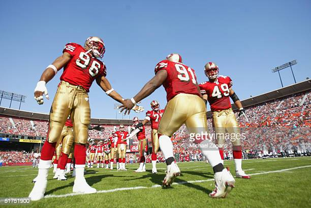 Andre Carter and Aaron Walker greet Anthony Adams of the San Francisco 49ers before the game against the Seattle Seahawks at Monster Park on November...