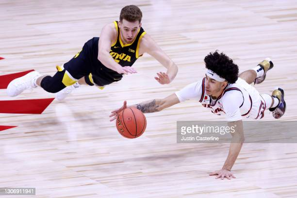 Andre Curbelo of the Illinois Fighting Illini and Jordan Bohannon of the Iowa Hawkeyes dive for the ball during the second half of the Big Ten men's...