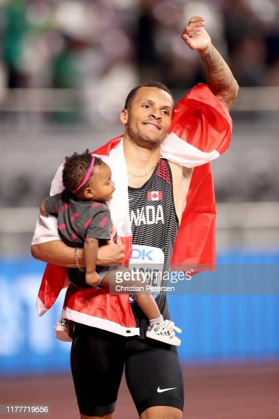 Andre De Grasse of Canada celebrates with his daughter Yuri after winning bronze in the Men's 100 Metres final during day two of 17th IAAF World...