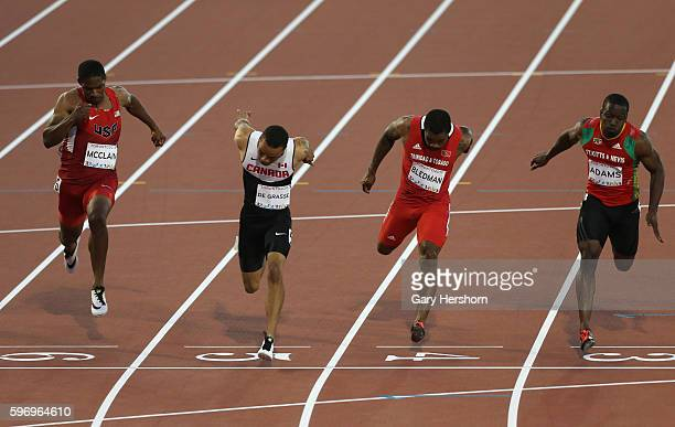 Andre De Grasse of Canada lunges at the finish line ahead of Remontay McClain of the USA Keston Bledman of Trinidad and Tobago and Antoine Adams of...
