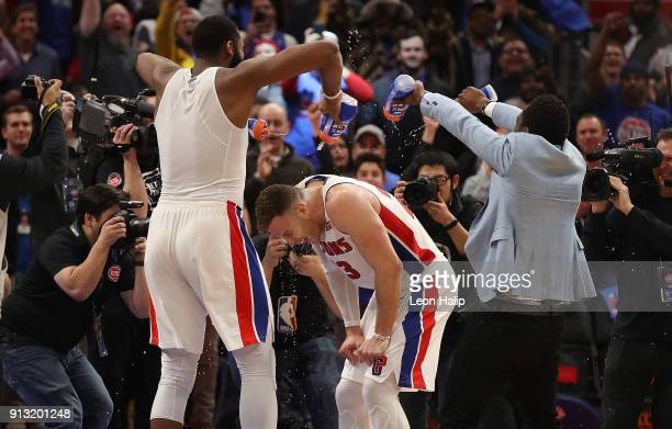 Andre Drummond and teammate Reggie Jackson celebrate Blake Griffin first win as a Detroit Pistons at Little Caesars Arena on February 1 2018 in...