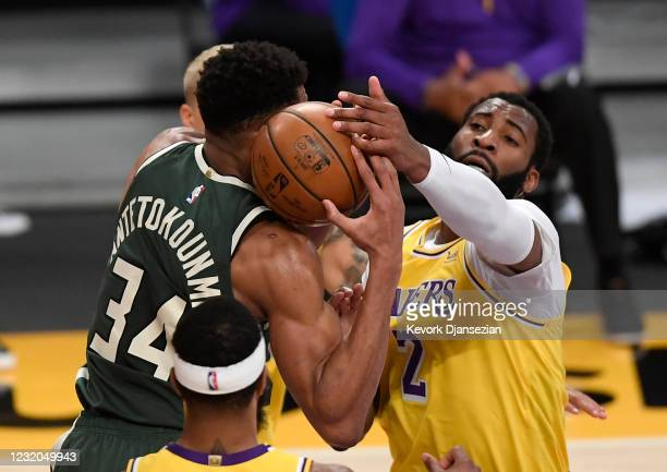 Andre Drummond, making his debut with the Los Angeles Lakers, and Giannis Antetokounmpo of the Milwaukee Bucks battle for rebound during the first...