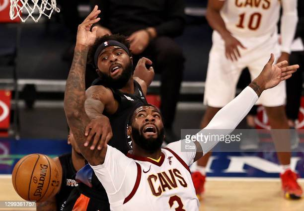 Andre Drummond of the Cleveland Cavaliers is fouled as he has for the net by Mitchell Robinson of the New York Knicks in the first quarter at Madison...