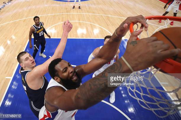 Andre Drummond of the Detroit Pistons dunks next to Nikola Jokic of the Denver Nuggets during the first half at Little Caesars Arena on February 04...