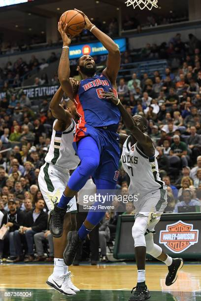 Andre Drummond of the Detroit Pistons is fouled by Khris Middleton of the Milwaukee Bucks during the second half of a game at the Bradley Center on...
