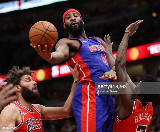 Andre Drummond of the Detroit Pistons rebounds between Robin Lopez and Justin Holiday of the Chicago Bulls at the United Center on January 13 2018 in...