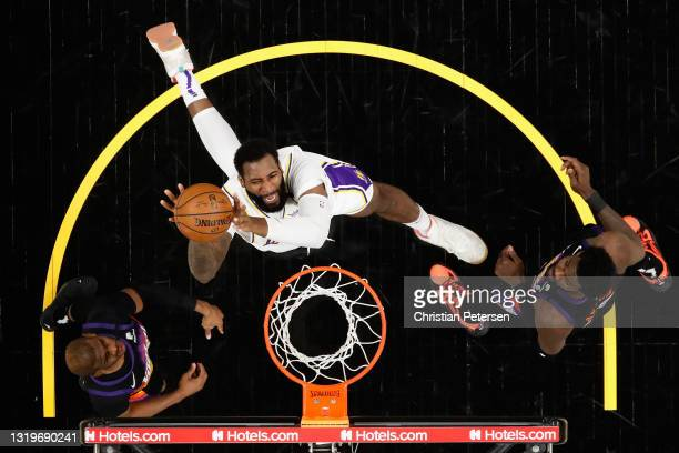 Andre Drummond of the Los Angeles Lakers attempts a shot over Chris Paul and Deandre Ayton of the Phoenix Suns during the second half of Game One of...
