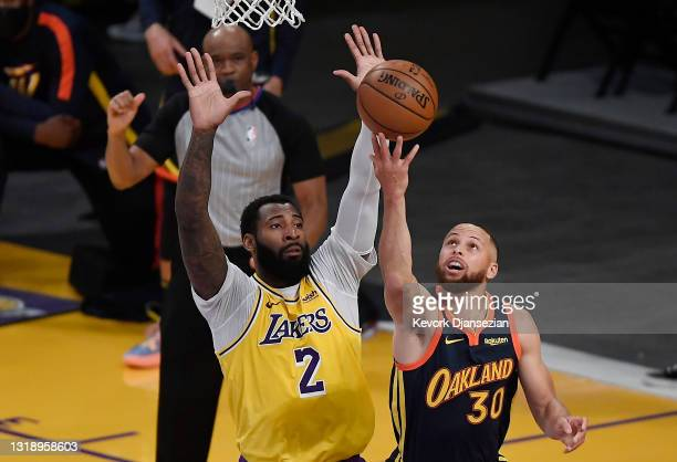 Andre Drummond of the Los Angeles Lakers guards Stephen Curry of the Golden State Warriors during the first half of an NBA Tournament Play-In game at...