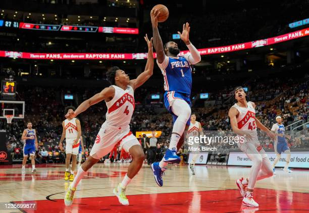 Andre Drummond of the Philadelphia 76ers goes to the basket against Scottie Barnes and Dalano Banton of the Toronto Raptors in preseason action at...