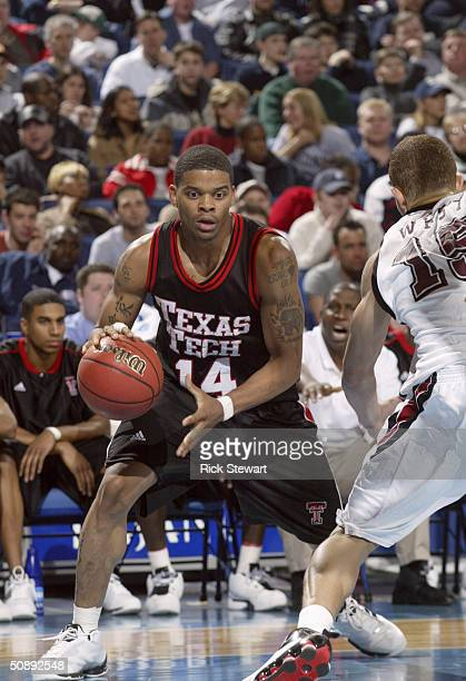 Andre Emmett of the Texas Tech University Red Raiders is defended by Delonte West of the St. Joseph's University Hawks during the second round of the...