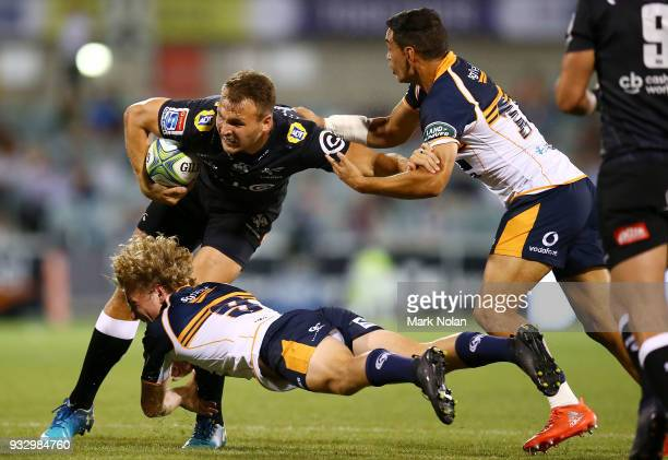 Andre Esterhuizen of the Sharks is tackled during the round five Super Rugby match between the Brumbies and the Sharks at GIO Stadium on March 17...