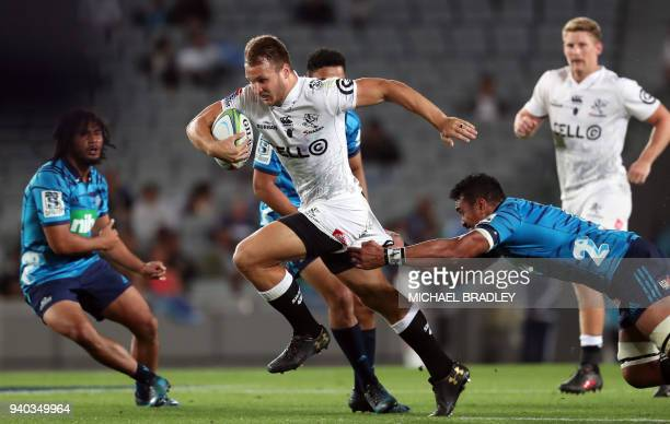 TOPSHOT Andre Esterhuzien of the Sharks breaks the tackles from the Blues' Jerome Kaino during the Super Rugby match between the Auckland Blues of...