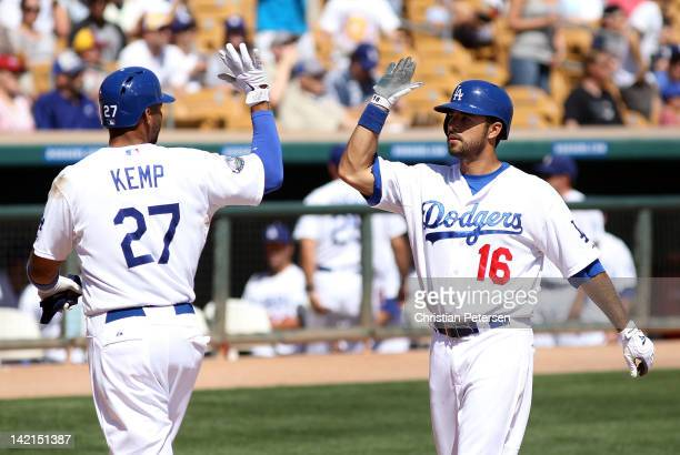 Andre Ethier of the Los Angeles Dodgers highfives Matt Kemp after Ethier hit a two run home against the Milwaukee Brewers during the third inning of...