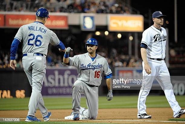 Andre Ethier of the Los Angeles Dodgers is congratulated by third base coach Tim Wallach as Chase Headley of the San Diego Padres looks on after...