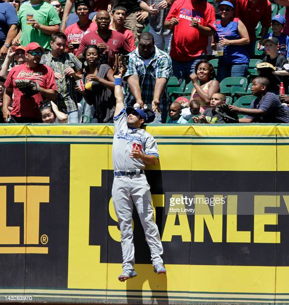 Andre Ethier of the Los Angeles Dodgers leaps but can't make a catch on a grand slam home run off the bat of Jordan Schafer of the Houston Astros in...