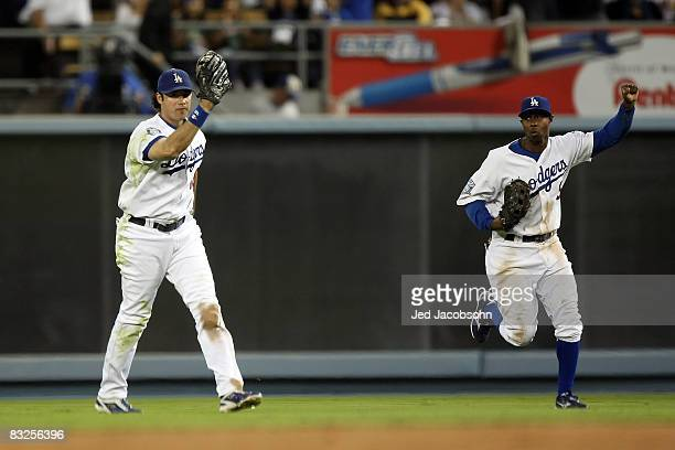 Andre Ethier of the Los Angeles Dodgers shows the ball after he makes a catch in right field alongside teammate Juan Pierre off a ball hit by So...