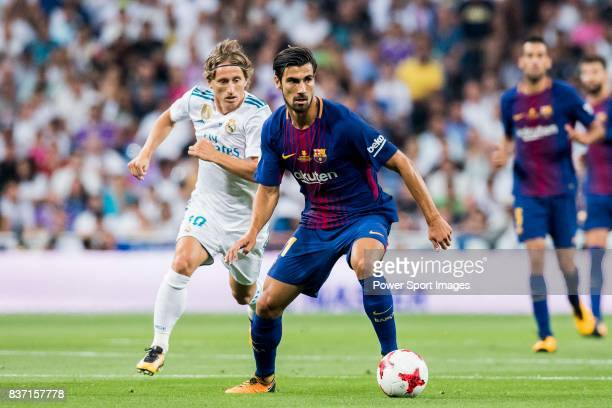 MADRID SPAIN AUGUST 16 Andre Filipe Tavares Gomes of FC Barcelona is followed by Luka Modric of Real Madrid during their Supercopa de Espana Final...