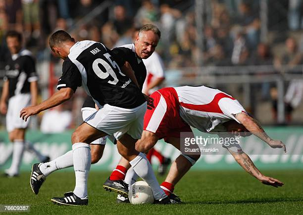 Andre Golke of the Hamburg team is challenged by Max Martin and Michael Rummenigge of the Germany team during the Day Of The Legends match at the...