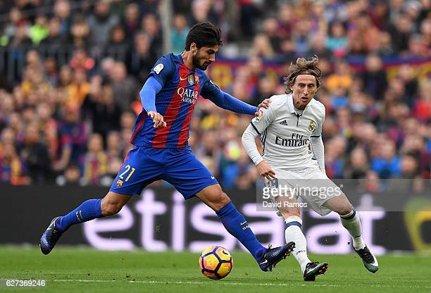 Andre Gomes of Barcelona and Luka Modric of Real Madrid compete for the ball during the La Liga match between FC Barcelona and Real Madrid CF at Camp...