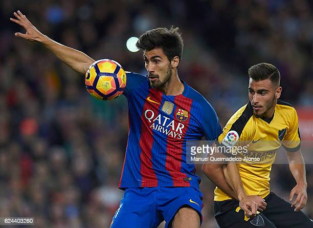 Andre Gomes of Barcelona competes for the ball with Juankar of Malaga during the La Liga match between FC Barcelona and Malaga CF at Camp Nou stadium...