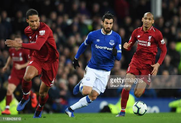 Andre Gomes of Everton goes between Virgil van Dijk and Fabinho of Liverpool during the Premier League match between Everton FC and Liverpool FC at...